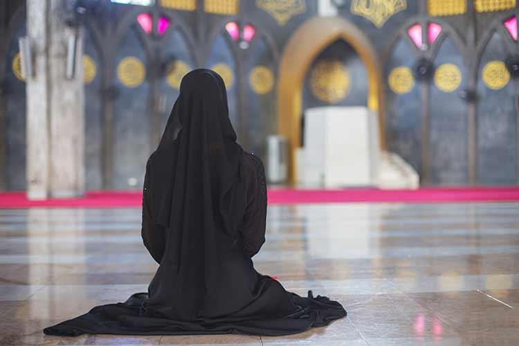 امرأة مسلمة شابة ترتدي فستان أسود تجلس وحدها في مسجد رؤية خلفية JBG