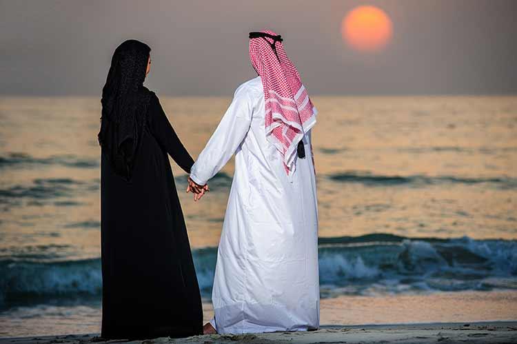 زوجان خليجيان على شاطيء البحر وقت الغروب JBG