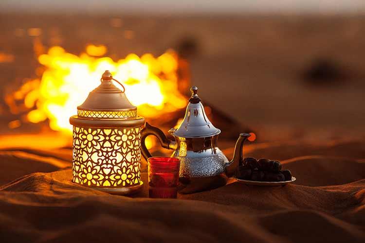 صورة تمور ابريق شاي فنجان قرب نار بالصحراء شهر رمضان JBG