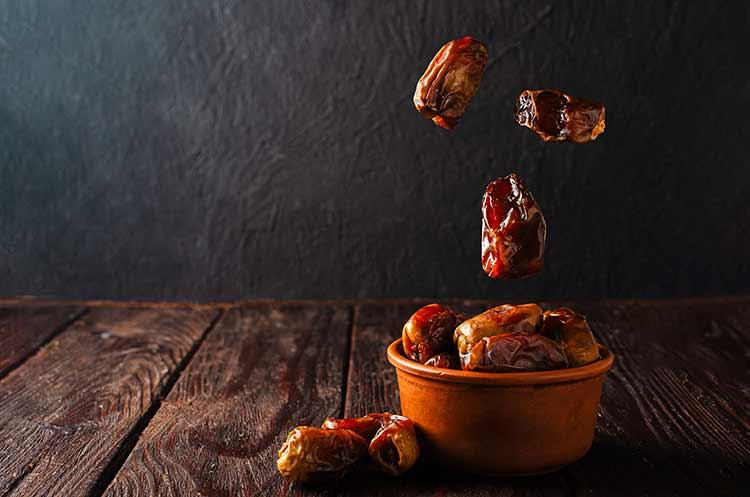 صورة طبق فخار مع التمر المجفف على مائدة خشبية شهر رمضان JBG