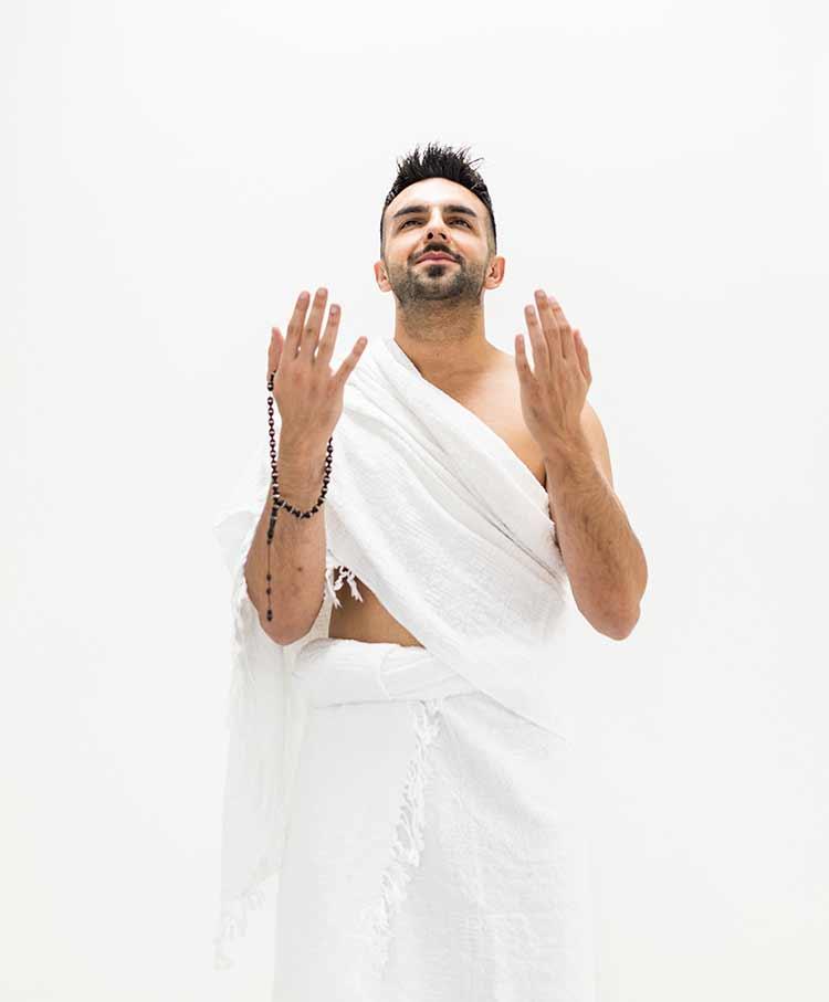 مسلم يرتدي الاحرام ممسك بيده مسبحه يدعو JBG