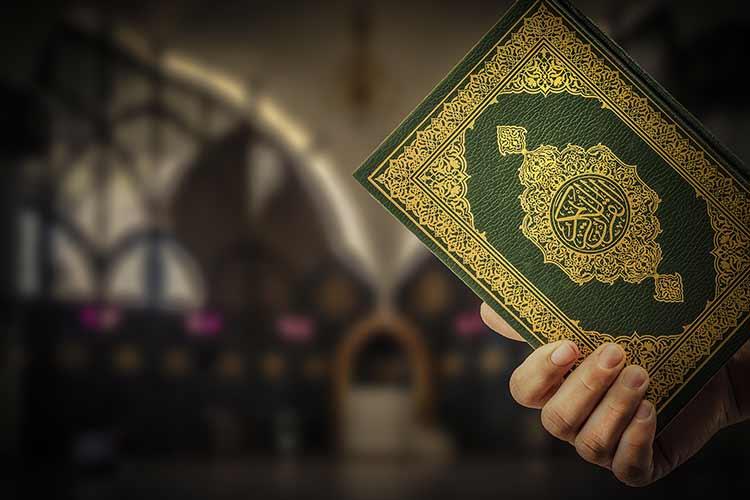 يد رجل مسلم تحمل القرآن الكريم مغلق JBG