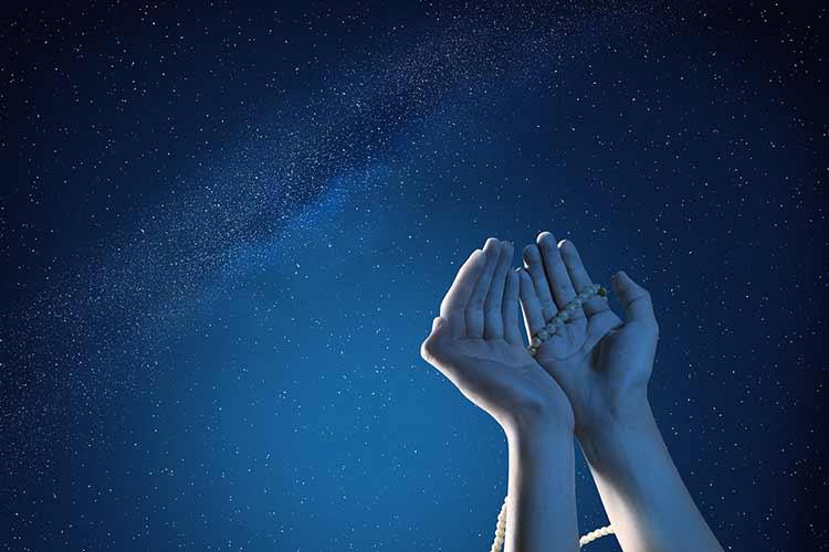 يد متجهه نحو السماء في المساء مع مسبحه تدعو JBG